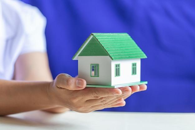 Manos humanas sosteniendo modelo de casa de ensueño.