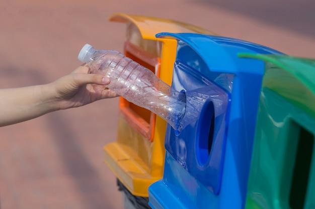 Las manos humanas tiran las botellas de plástico a la basura equivocada.