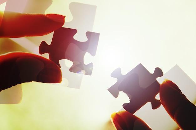 Manos humanas uniendo las piezas del rompecabezas en el fondo