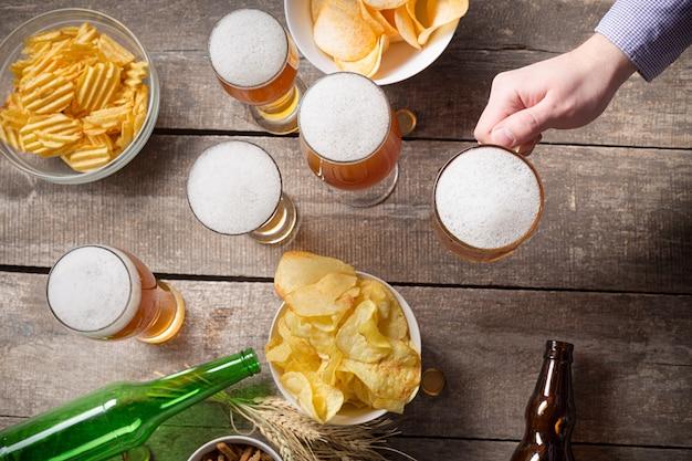 Manos humanas y vasos de cerveza
