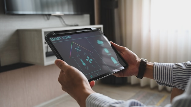 Las manos con imagen recortada están usando una tableta con aplicaciones controladas por dispositivos domésticos en la pantalla.