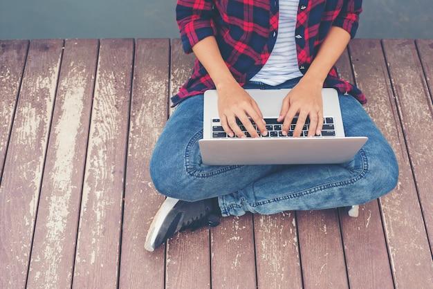 Manos inconformista joven que pulsa ordenador portátil sentado en el muelle de lago, relajante