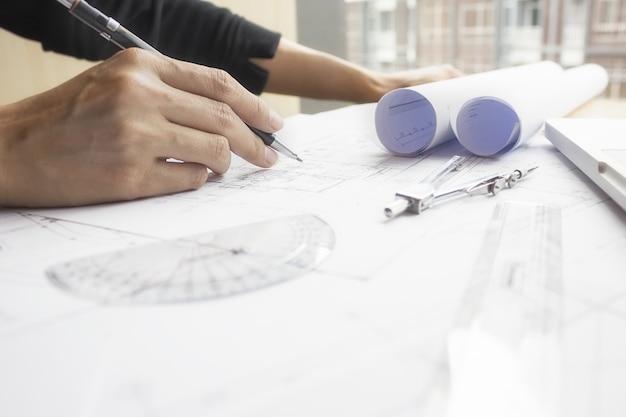 Manos del ingeniero que trabajan en blueprint, concepto de la construcción. herramientas de ingeniería.vintage efecto de filtro retro tono, enfoque suave (enfoque selectivo)