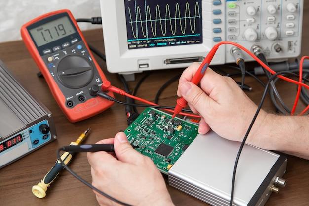 Manos del ingeniero con sondas que prueban el voltaje en la placa
