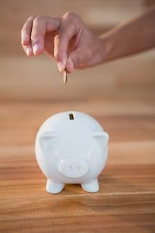 Manos a la inserción de monedas en la hucha