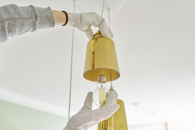 Manos instalando bombilla led en lámpara, candelabro