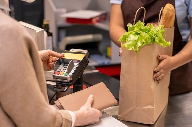 Manos del joven cajero en la bolsa de papel con alimentos frescos delante del comprador femenino maduro pagando productos con tarjeta de crédito