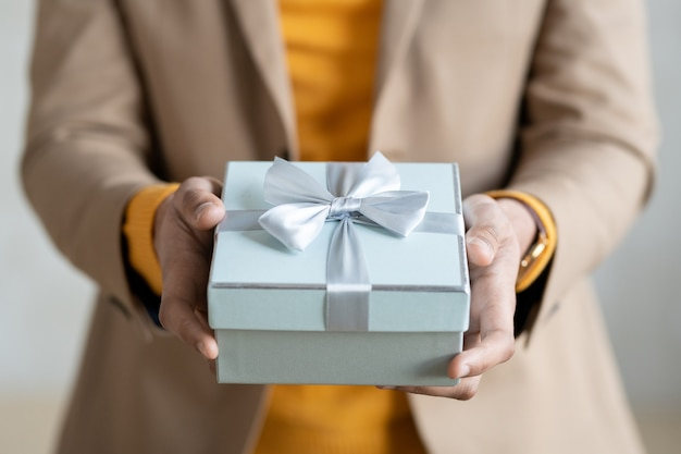 Manos del joven empresario elegante en ropa casual elegante que le pasa empacó el regalo en caja de regalo azul claro con lazo de cinta de seda en la parte superior