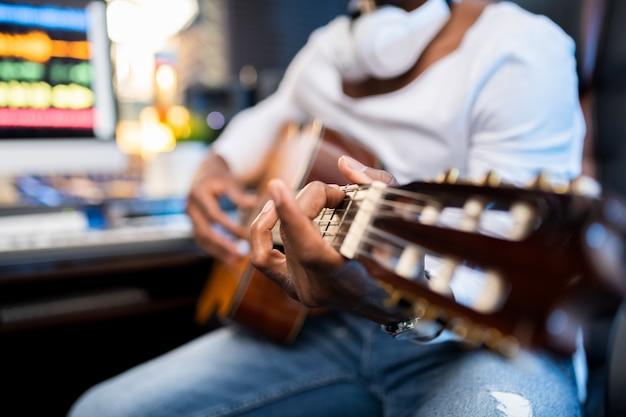 Manos de joven músico de etnia africana en cuerdas de guitarra acústica durante el proceso de canto o grabación de sonido