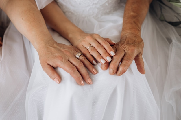 Manos de una joven novia y las manos de los padres, diferente generación, día de la boda