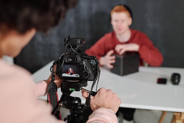 Manos de joven operador por cámara disparando vlogger masculino contemporáneo desembalaje caja por escritorio en estudio
