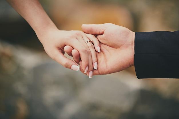 Manos de una joven pareja con un anillo.