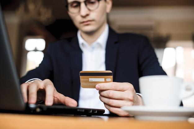 Manos de un joven sosteniendo una tarjeta de crédito dorada y trabajando en una computadora portátil vestida con traje sentado en un escritorio.