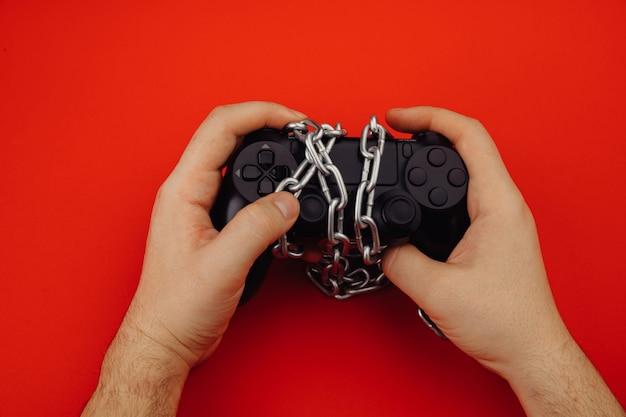 Las manos de un joven sostiene un dispositivo de juego atado con una cadena.