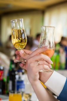 Manos de jóvenes con copa de vino.