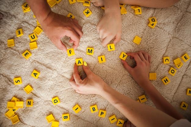 Manos jugando scrabble juego en la alfombra en casa