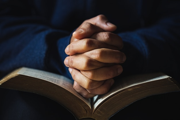 Las manos juntas en oración sobre una santa biblia en el concepto de iglesia para la fe