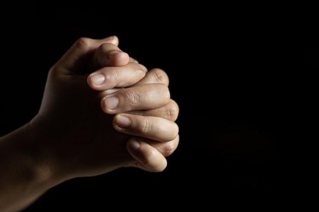 Manos juntas en oración