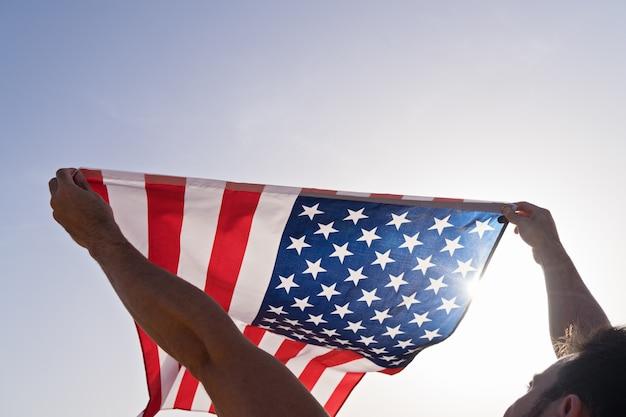Manos levantadas del hombre con ondeando la bandera americana contra el cielo azul claro