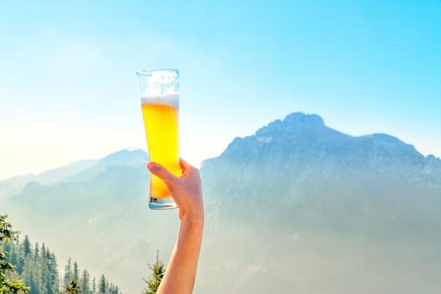 Manos levantando el vaso de cerveza de barril y feliz disfrutando de la cosecha en el exterior en la hermosa escena de montaña