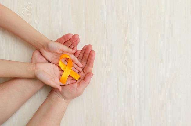 Las manos de la madre y el niño sostienen la cinta naranja sobre fondo blanco día mundial de la esclerosis múltiple