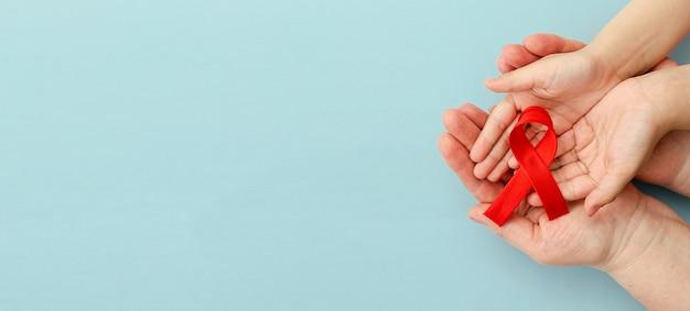 Las manos de la madre y el niño sostienen la cinta roja día de la hemofilia dar transfusión de sangre y donación