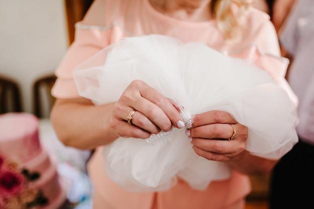 Manos de la madre sosteniendo cintas y ayudando a vestir a la novia por la mañana. dama de honor preparando a la novia para el día de la boda, ayudando a sujetar el velo. preparándose. preparativos del concepto de boda.