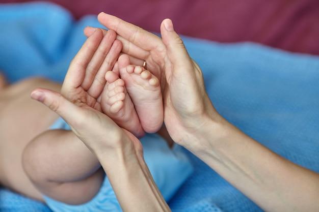 Manos de la madre sosteniendo cuidadosamente los pies del bebé, enfoque selectivo