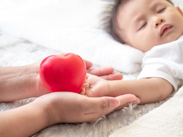 Manos de la madre sosteniendo las manos del bebé con un corazón rojo. día de la madre y cuidado, familia, protección, amor.