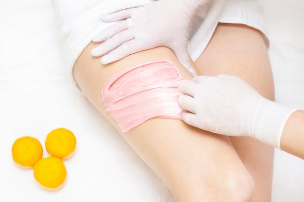 Las manos de un maestro azucarador aplican pasta azucarada rosa en las caderas de una niña. en el fondo es una mandarina. concepto de depilación centro de spa y salón de belleza.