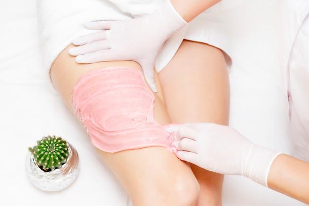 Las manos de un maestro shugaring aplican una pasta rosada shugaring en las caderas de una niña. en el fondo es un cactus.