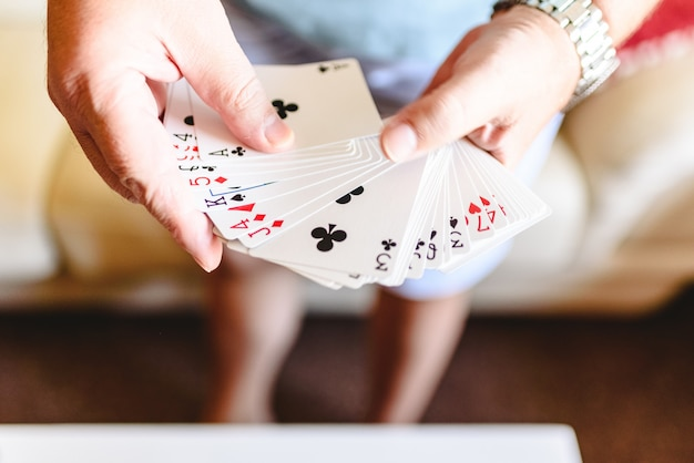 Manos de mago haciendo truco de magia con naipes.