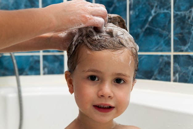 Las manos de mamá lavando la cabeza de la pequeña niña en el baño.