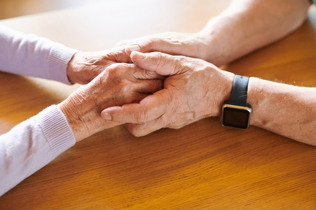 Manos del marido maduro solidario sosteniendo las de su esposa delante de él sobre la mesa de madera
