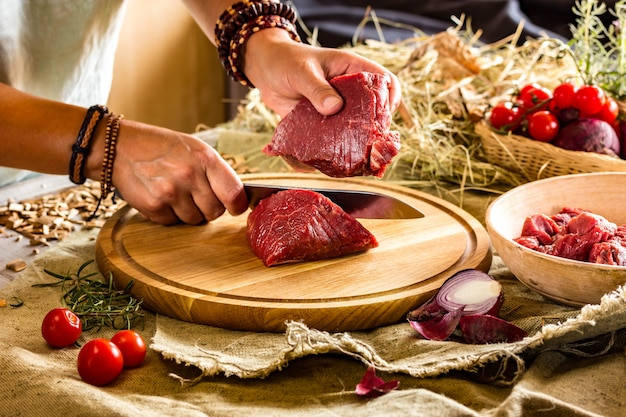 Las manos marrones en pulseras cortan carne fresca