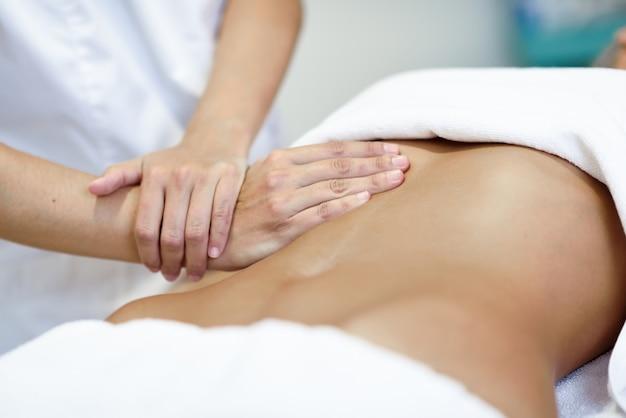 Manos masajear abdomen.therapist femenino aplicar presión sobre el vientre.