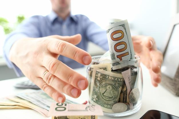 Manos masculinas agarrando gran frasco gordo lleno de moneda estadounidense como gesto de avaricia