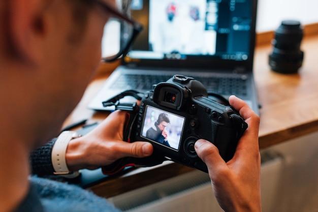 Manos masculinas con cámara profesional, mira fotos, sentado en el café con la computadora portátil.