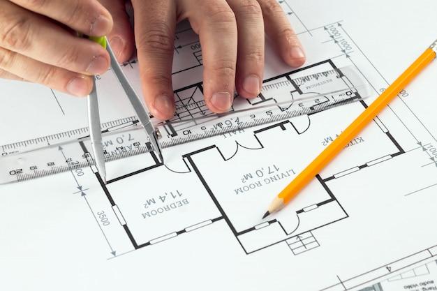 Manos masculinas, casco naranja, lápiz, planos arquitectónicos, cinta métrica.