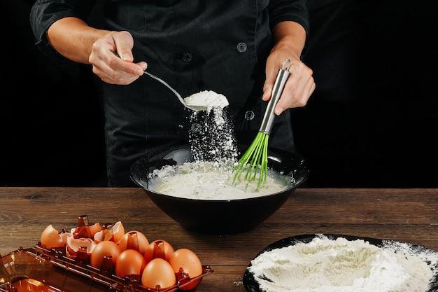 Manos masculinas chef vierte la harina en un plato sobre una mesa de madera marrón en utensilios negros