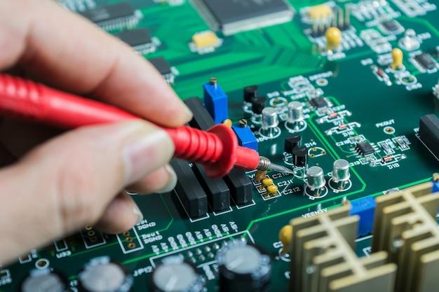 Las manos masculinas se cierran encima de controlar voltaje en el transistor
