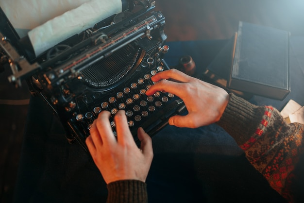 Manos masculinas escribiendo en máquina de escribir retro