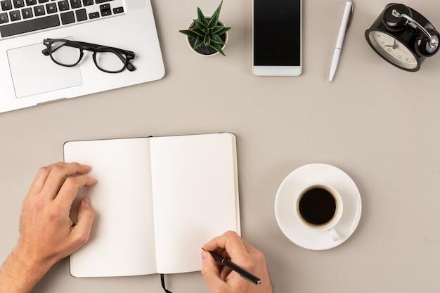 Manos masculinas escribiendo en la página de bloc de notas vacío en el escritorio de la oficina moderna frente a la computadora portátil