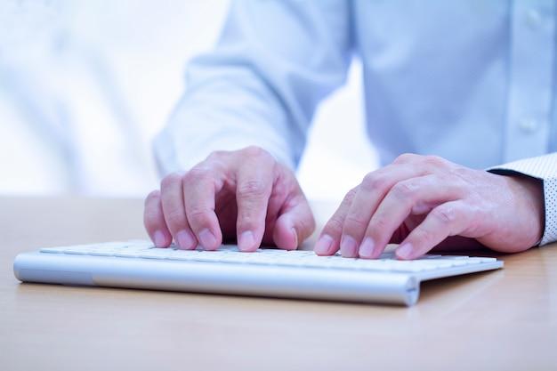 Manos masculinas escribiendo en un teclado de computadora blanco moderno