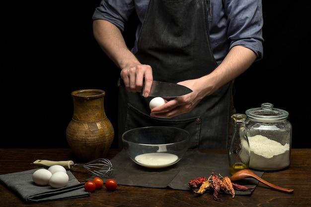 Las manos masculinas están rompiendo un huevo en un recipiente de vidrio para hacer masa.