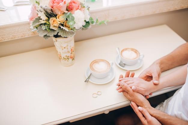 Las manos masculinas están sosteniendo las manos femeninas. mano femenina con un anillo de bodas. manos masculinas confiables. fuertes manos masculinas.