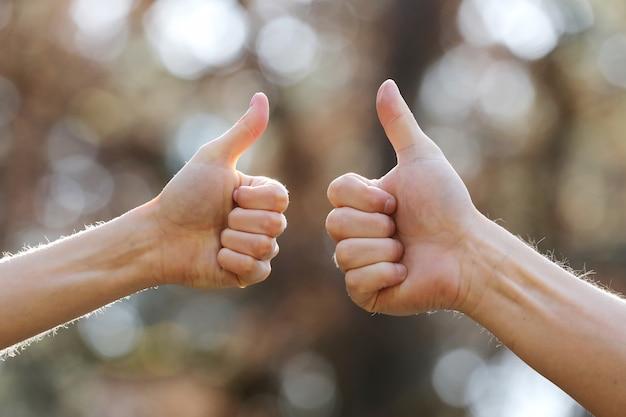 Manos masculinas y femeninas que muestran los pulgares para arriba al aire libre. las manos muestran bien sobre fondo natural. enfoque selectivo