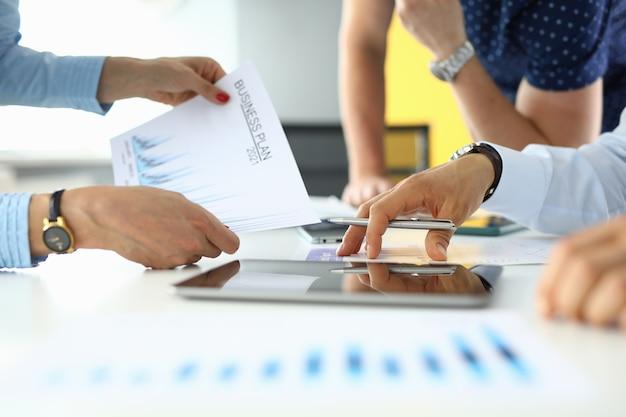 Manos masculinas y femeninas tienen un plan de negocios y un bolígrafo