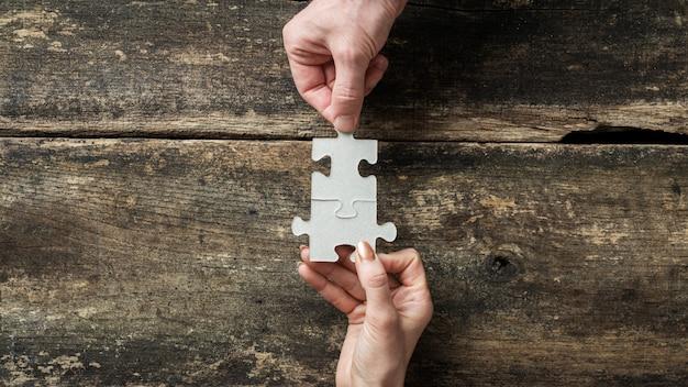 Manos masculinas y femeninas uniendo dos piezas de rompecabezas a juego
