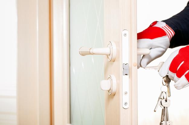 Las manos masculinas en guantes ponen la llave en el ojo de la cerradura. concepto de seguridad y protección del hogar.